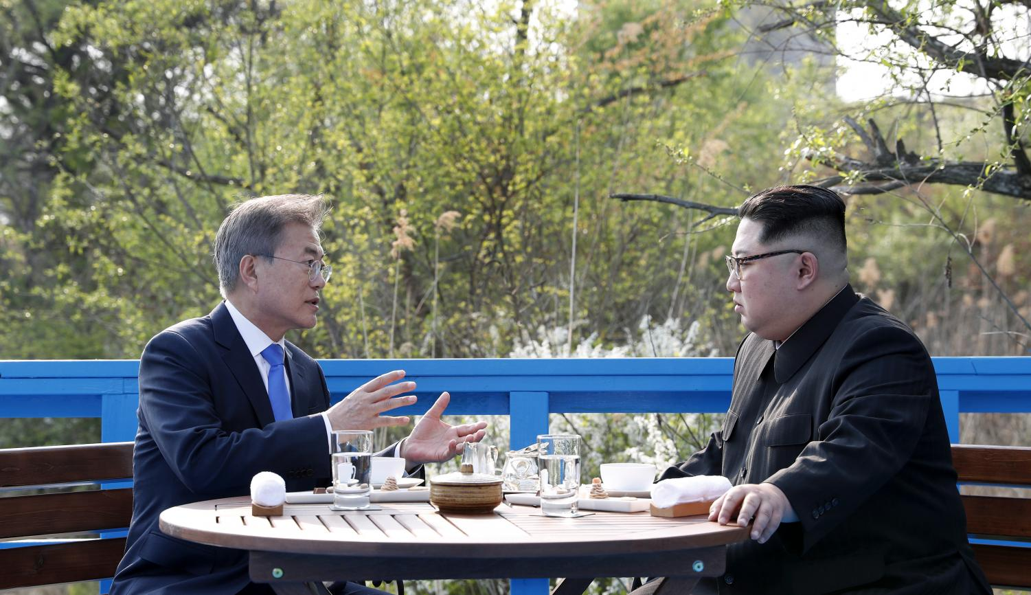 President Moon Jae-in and Chairman of the State Affairs Commission Kim Jong Un share conversations while they take a walk on the Footbridge, where there is a sign for the Military Demarcation Line (MDL) in Panmunjeom on April 27.