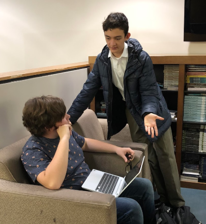 Brendan Huston, sophomore representative for the MUN Club, assists a club member at a position paper workshop on Wednesday.